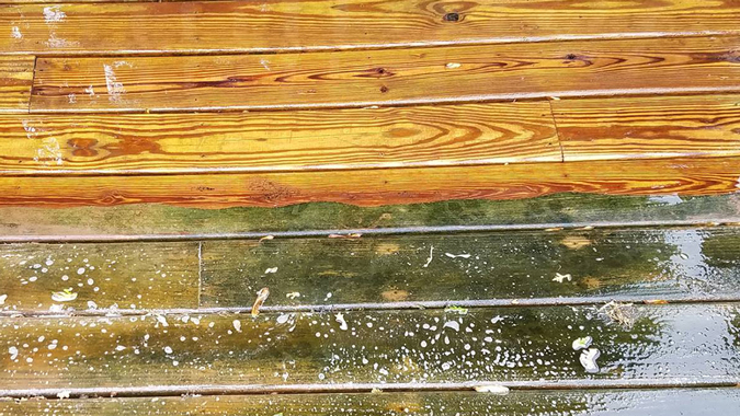 Half of a wood deck pressure washed to show before and after
